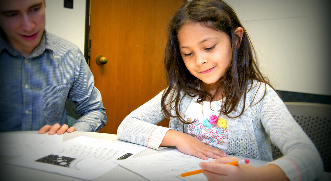 A girl works on a set of problems at the UIC Assessment Clinic, where students from the MEd Special Education program intern to diagnose potential special education needs.