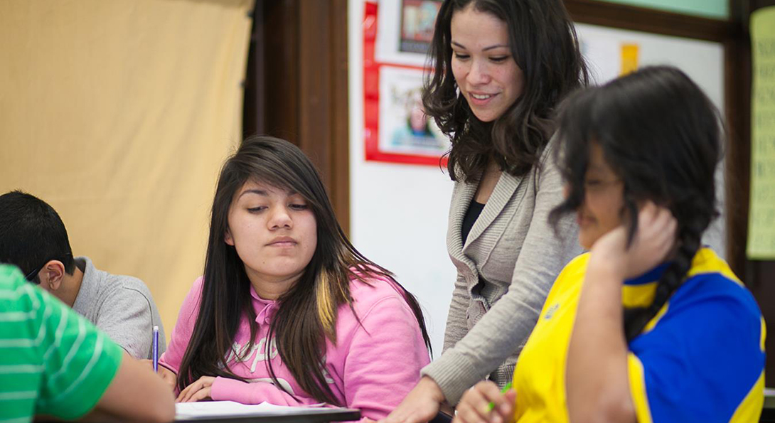 Jasmine Juarez stands over two girls who are sitting next to each other at desks, and Juarez offers input on the math assignment they are working on.