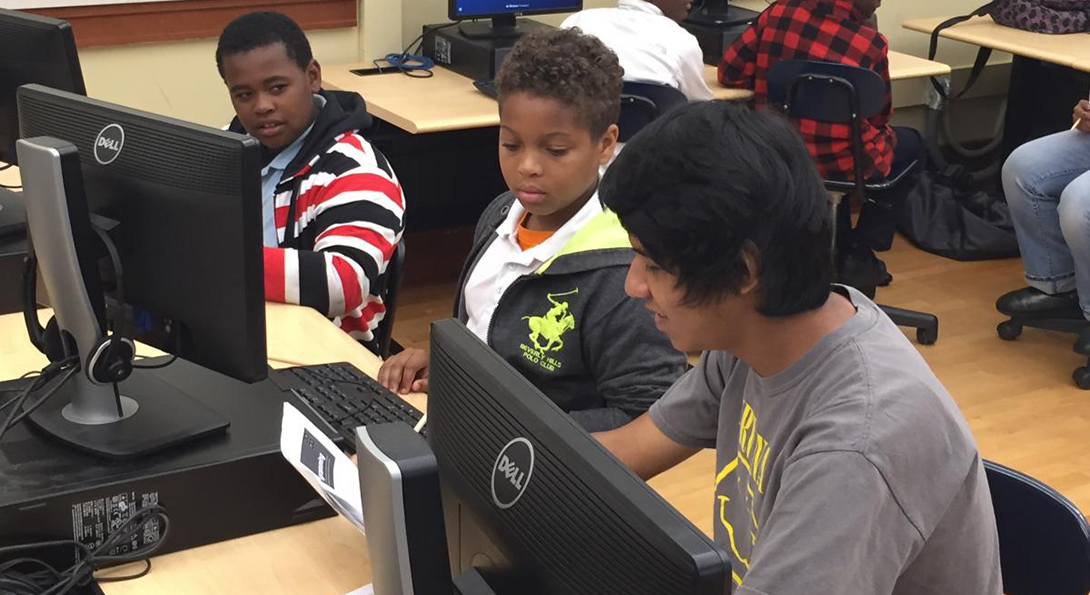 Three students sit at a row of computers, typing and working on a computer coding task. Two of the students are elementary students working with the third student, who is a high school mentor.