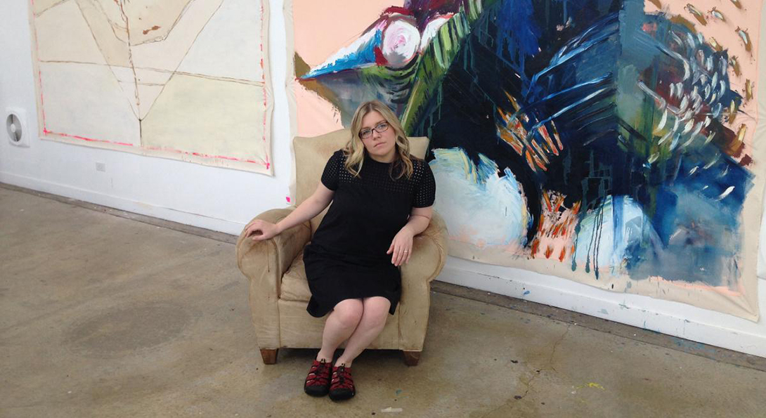 Rachel Harper sits in an easy chair in front of a large work of art, an abstract painting, in an art gallery.