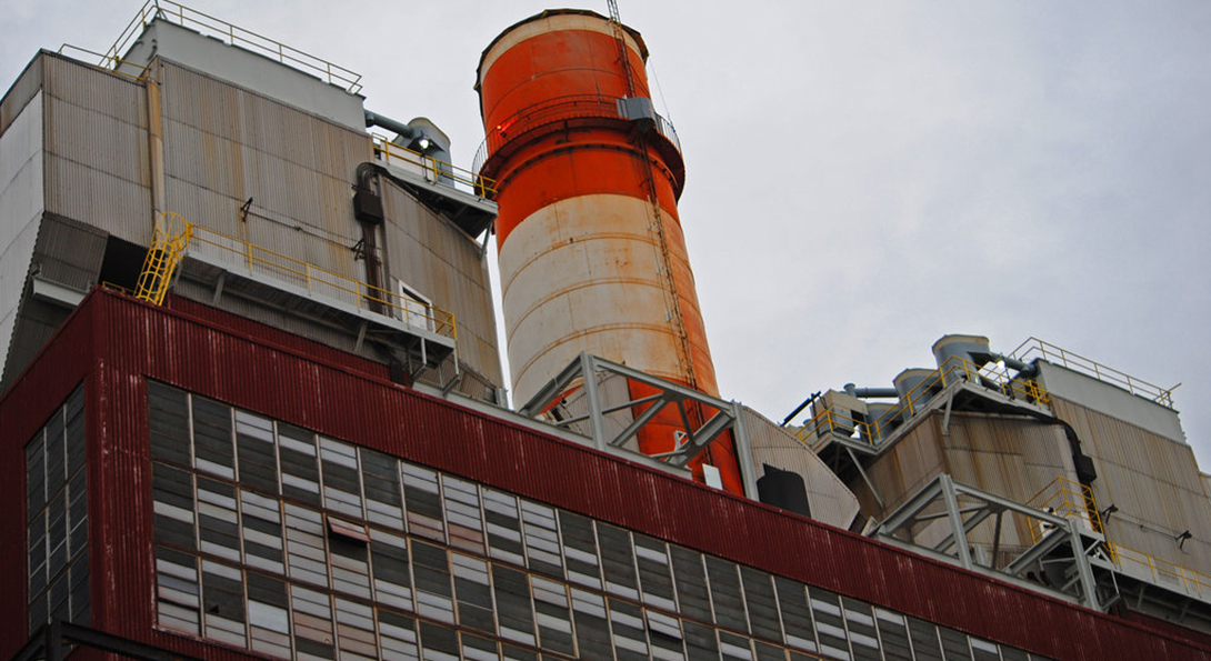 The Crawford Generating Station, a now-retired coal plant in Chicago.  A rusted orange smokestack rises above a series of boarded up window panes on a large red brick building.
