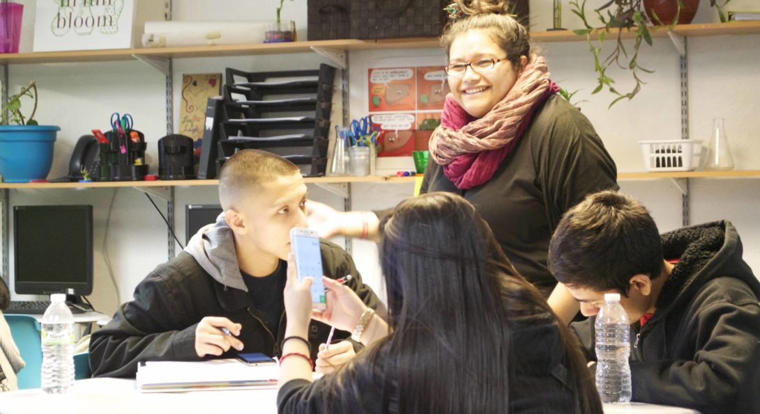 Teacher Adilene Aguilera stands by a group of three students sitting at a table, discussing their current science experiment with them.