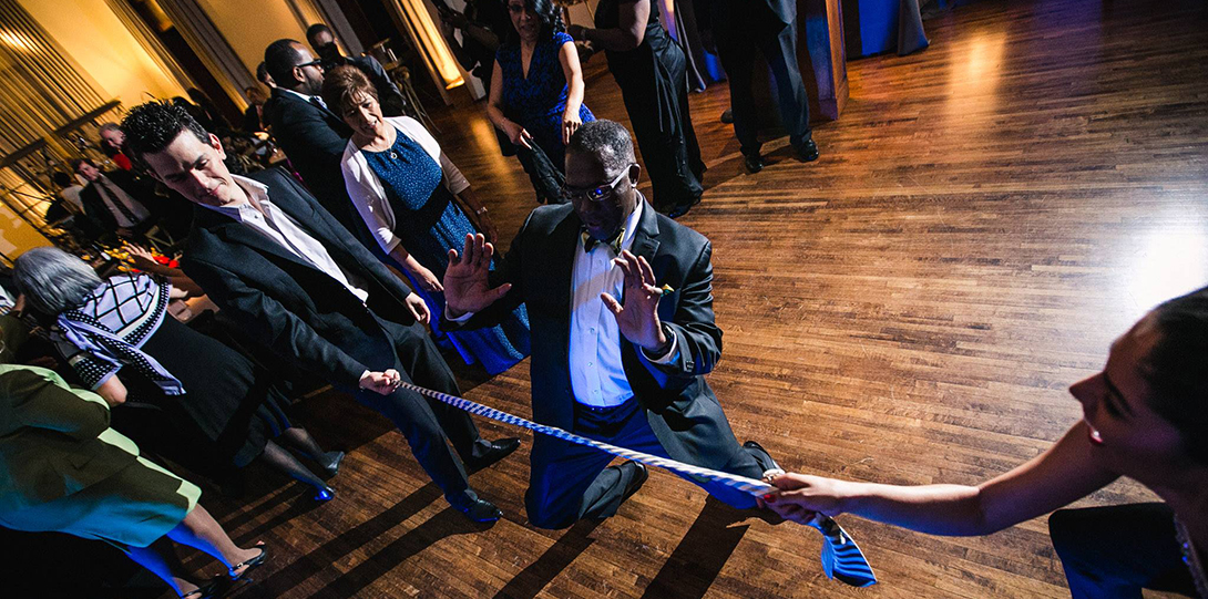 College Dean Alfred Tatum dances the limbo, with two others on the dance floor holding the limbo pole.  A number of other gala attendees are watching on the dance floor.