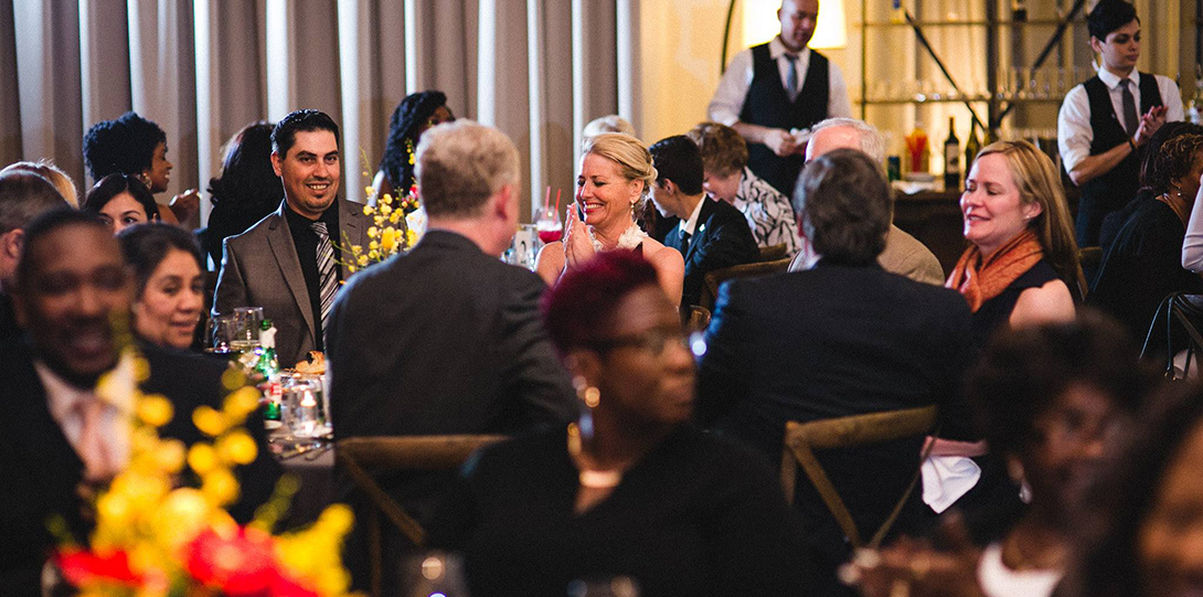 Attendees at the 2016 Alumni Honors gala sit around tables having conversations and eating dinner.