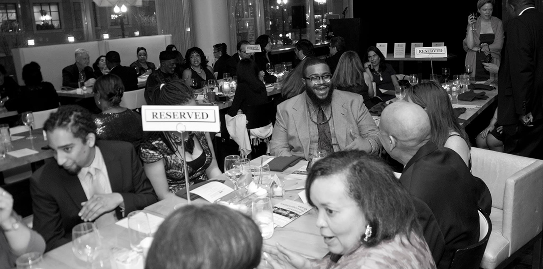 Guests enjoy dinner, seated at long tables, at the 2014 Alumni Honors Gala.