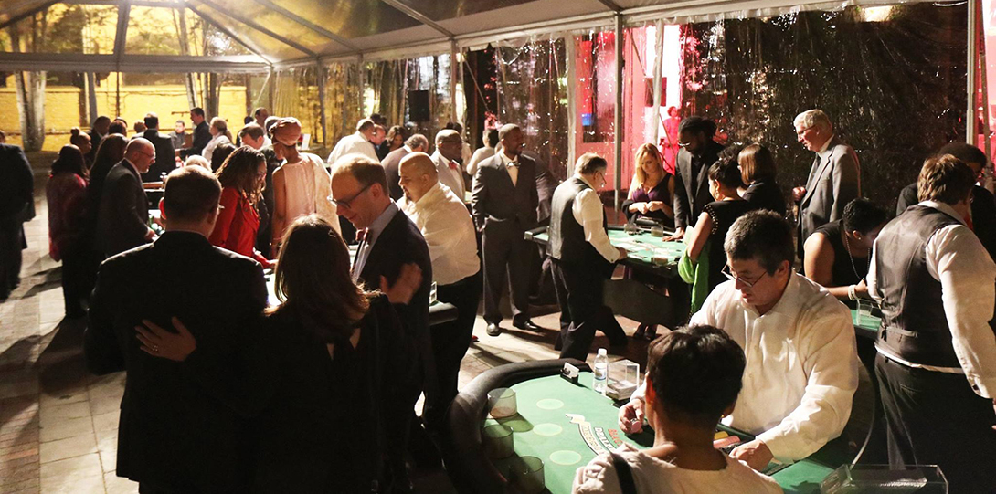 Guests are mingling and playing casino games in a large outdoor tent at the 2017 Alumni Honors Gala.