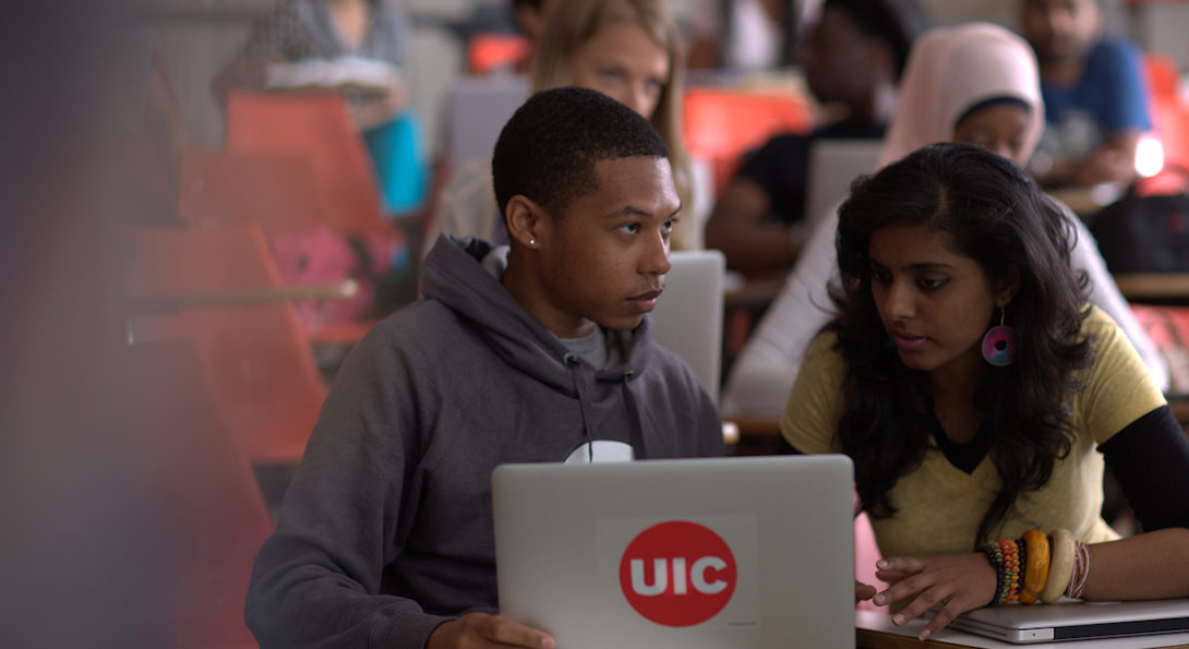 Two students are looking at content on a laptop in a UIC lecture hall, with a number of students sitting at desks behind them.