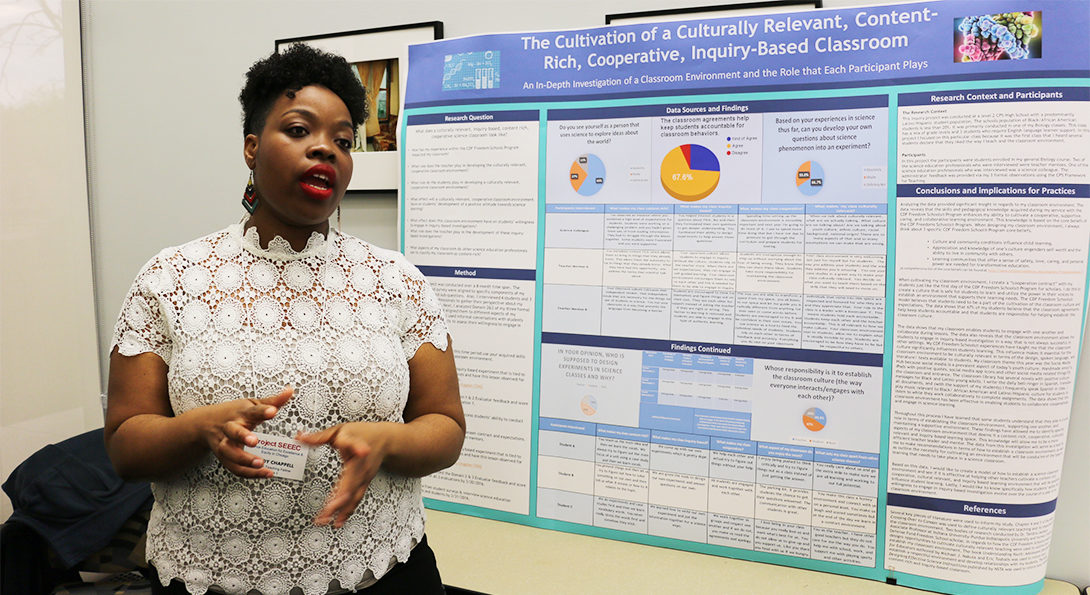 Doctoral student Mindy Chappell explains the results of a research project she conducted in her science classroom, standing in front of a large poster displaying her research results.