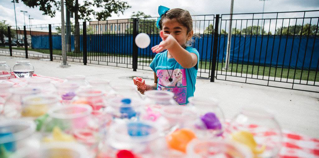 A young girl tosses a ping pong ball toward an array of plastic fishbowls, each containing a prize earned by getting the ball into a fishbowl.