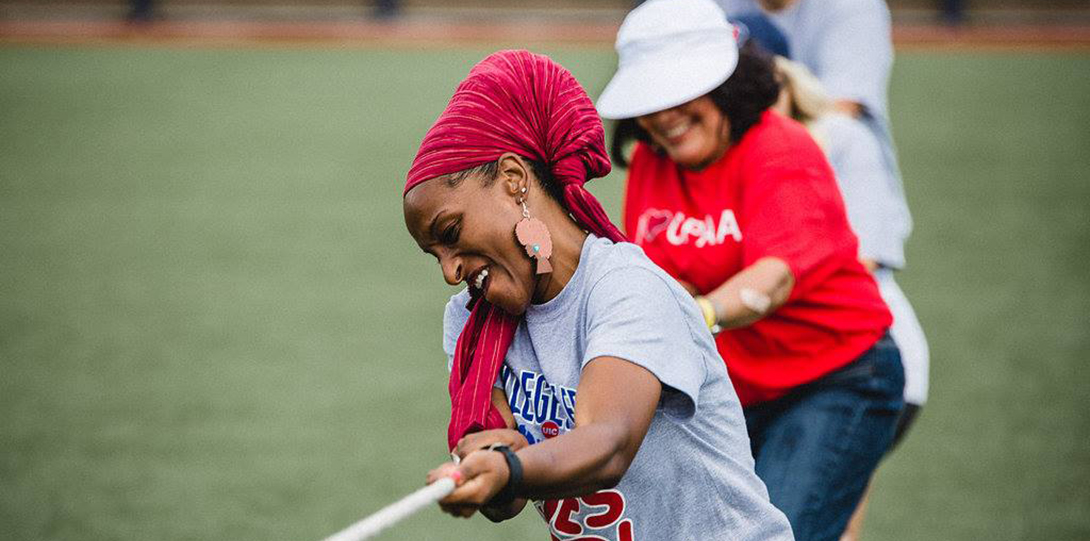 Three attendees are smiling and furiously pulling a rope, their bodies at angles with the ground, during a game of tug-of-war.
