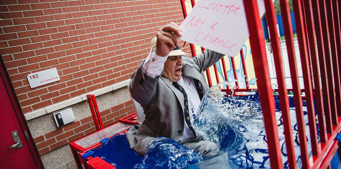 Professor Steve Tozer falls into a pool of water in a dunk tank, after an attendee at the College of Ed Goes Red event successfully struck the lever with a ball to sendhim into the water.  Tozer is holding a sign that says