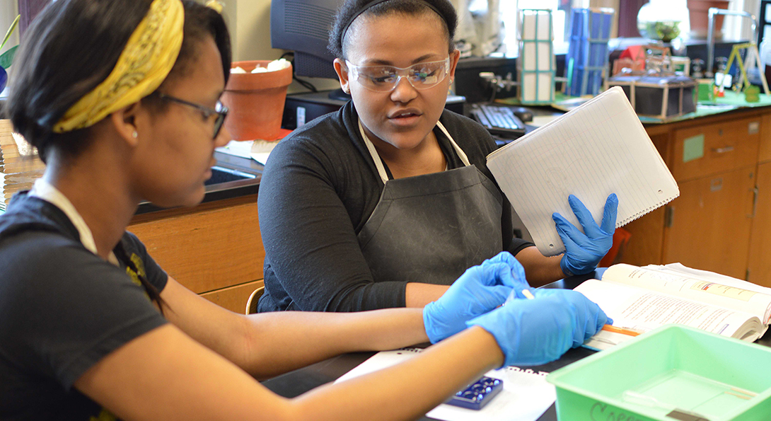 Two Black girls work on a science experiment, removing liquid from a vial and transferring it to a beaker.