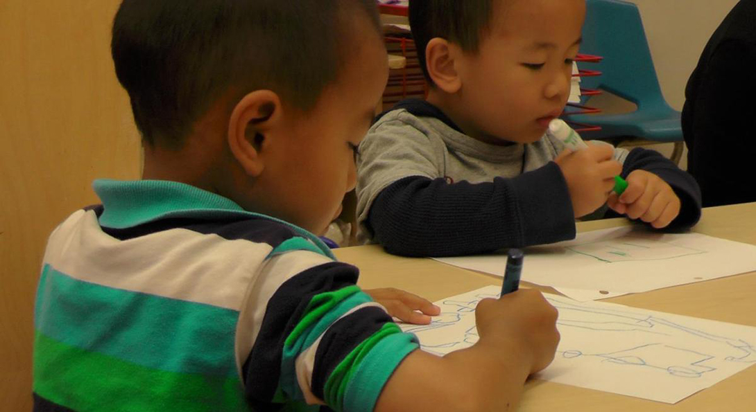Two students work on a drawing at the Chinese American Service League early childhood center.