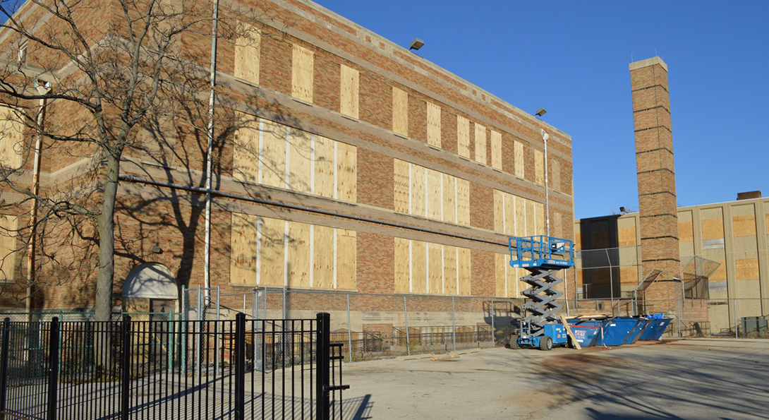 A closed CPS school has its windows and doors boarded with plywood, and a retractable crane platform sits outside the building.