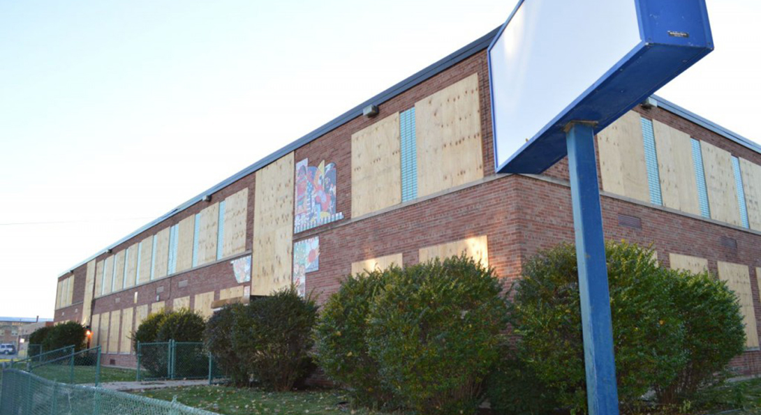 A closed CPS school has its windows and doors boarded up with plywood.