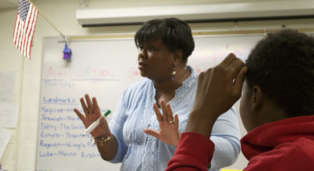 Teacher Debra Thomas leads a discussion in a self-contained special education classroom as one student listens to her speak.