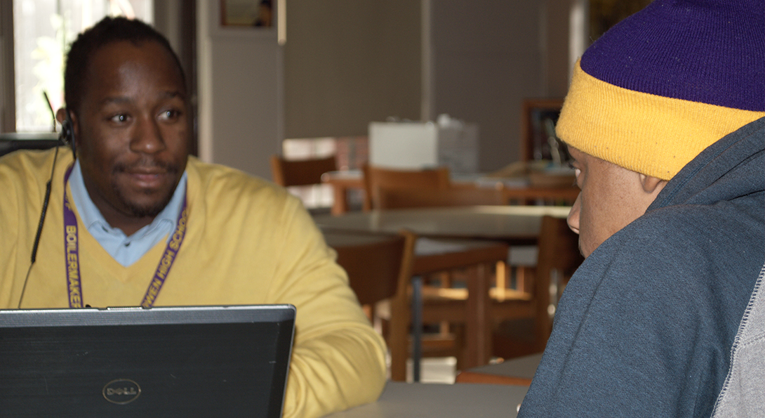 Teacher Eugene Robinson talks one-on-one with a Black male student at CPS Bowen High School, in the school's library.