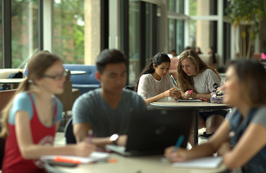 Students sit at a table working on homework together in UIC's Student Center East.  One student is typing on a laptop while the other two are engaged in a discussion and writing in notebooks.