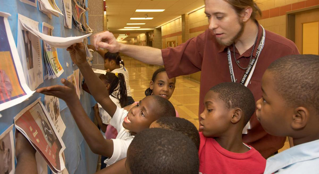 A teacher is looking at examples of student art on a bulletin board in a school hallway, surrounded by young Black male students.