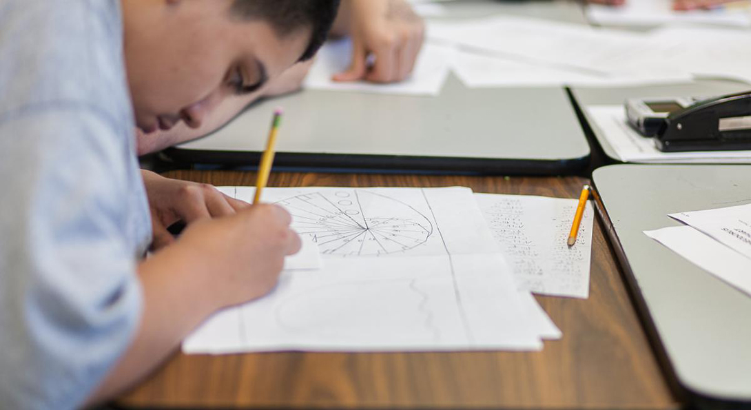 A Latino student works on a math problem with pencil and paper sitting at a desk in a classroom.