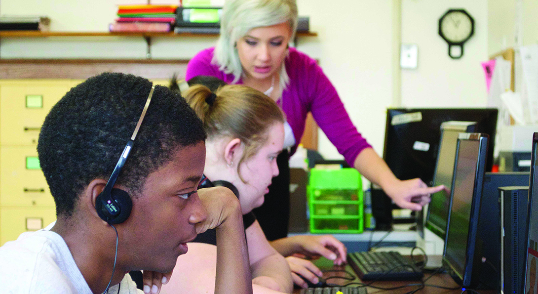 Special education teacher Samantha Rosell instructs two students who are sitting at computers playing a game that develops skills with word identification.