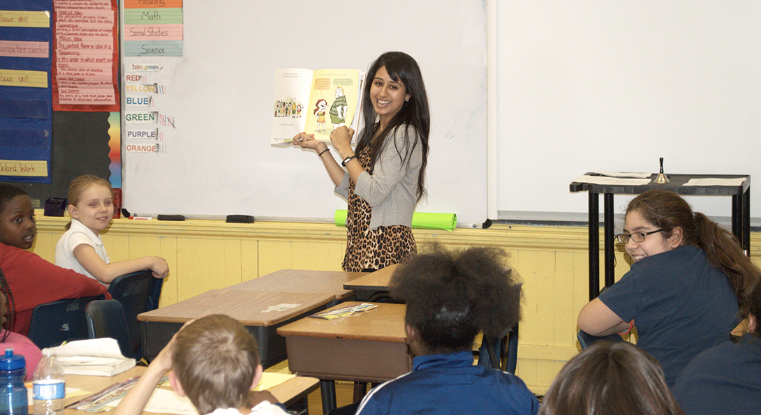 Yasmeen Elayyan is teaching a class, holding up a children's book as part of a read-aloud with her students.  One student is answering a question, and the rest of the students are looking at her.