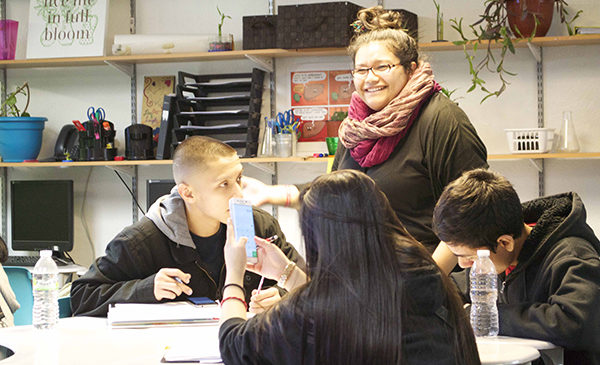 Teacher Adilene Aguilera stands over a table where three students are seated, having a conversation with them about the science experiment they are currently working on.