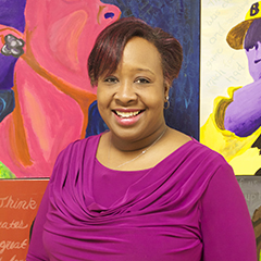 Carlitta Tucker-Powell poses for a photo standing against a colorful mural at Gwendolyn Brooks College Prep.