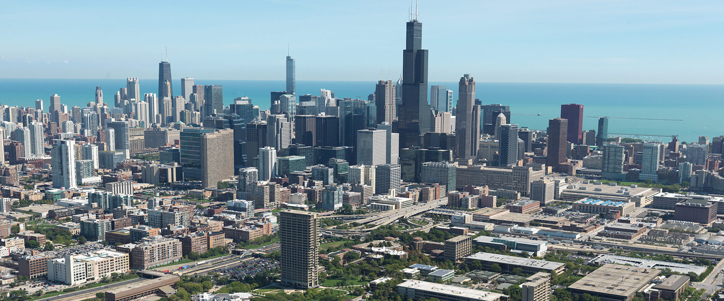 An aerial view of the Chicago skyline, with the UIC campus in the foreground, including University Hall and the College of Education building, and Lake Michigan in the background.
