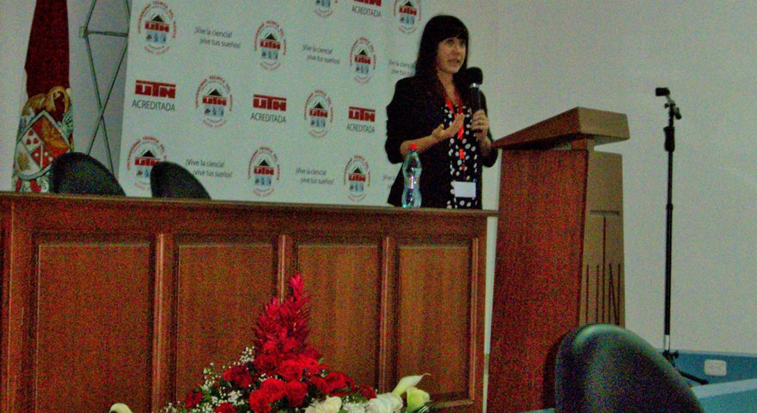 Alumna Alexis Cullerton stands behind a podium holding a microphone delivering a speech to educators in Educador on English education for teachers.