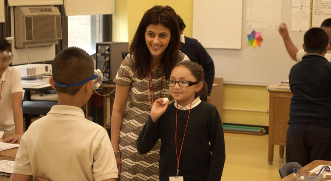 Teacher Amani Ghusein stands behind two students who are running a science experiment, in which one student throws a cotton ball at the face of the second student, to test the second student's blinking reflexes.  The second student is wearing safety goggles.