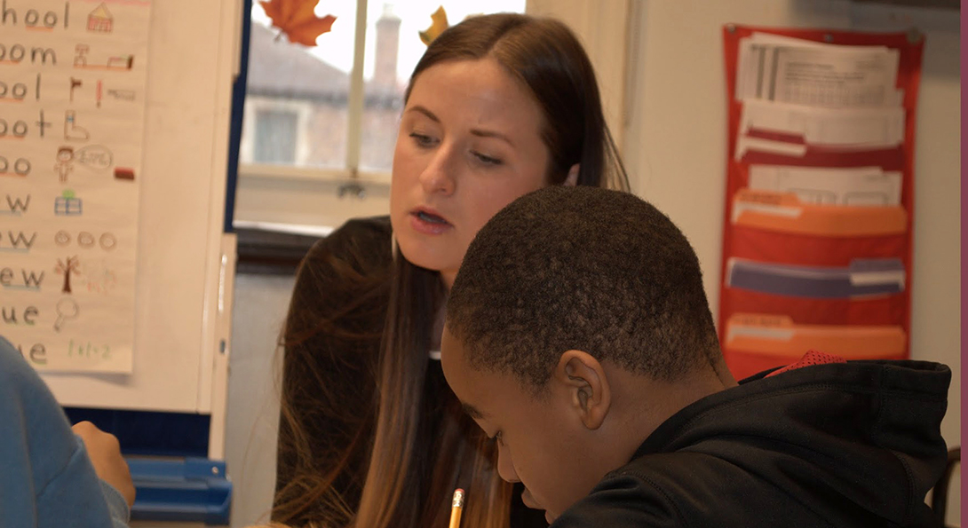 Anne Kellogg sits at a table with a Black male student with special education needs.  She is providing one-on-one guidance toward an assignment the student is working on.  The student is writing on a piece of paper with a pencil.