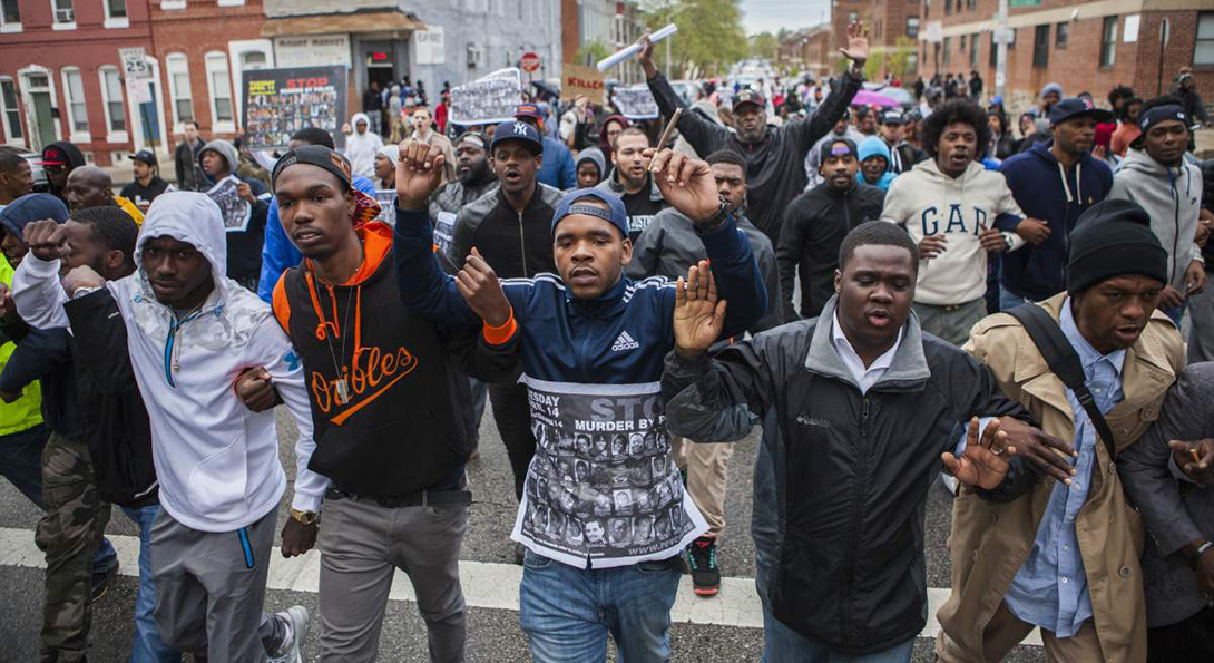 Baltimore citizens march with hands raised as a protest to the police killing of Freddie Gray.
