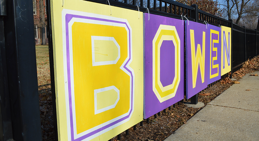 Five wooden boards hang from a fence outside Bowen High School, spelling out the school name with capital letters B, O, W, E and N, painted in purple and yellow, the school colors.