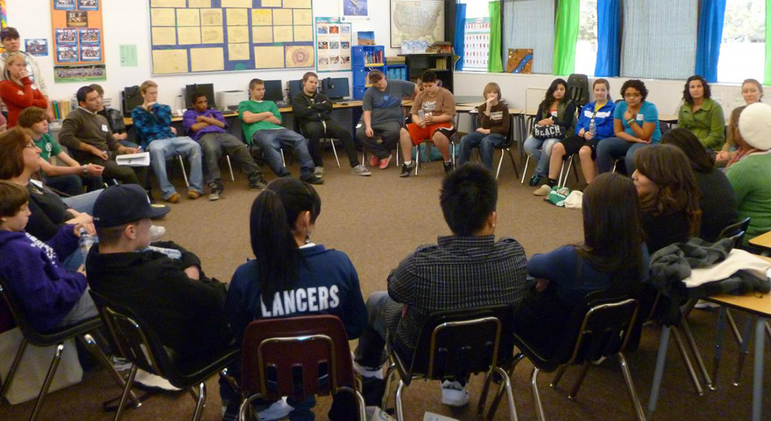In a classroom, about 30 students sit in a peace circle, seeking to resolve inter-personal conflicts through peaceful means.