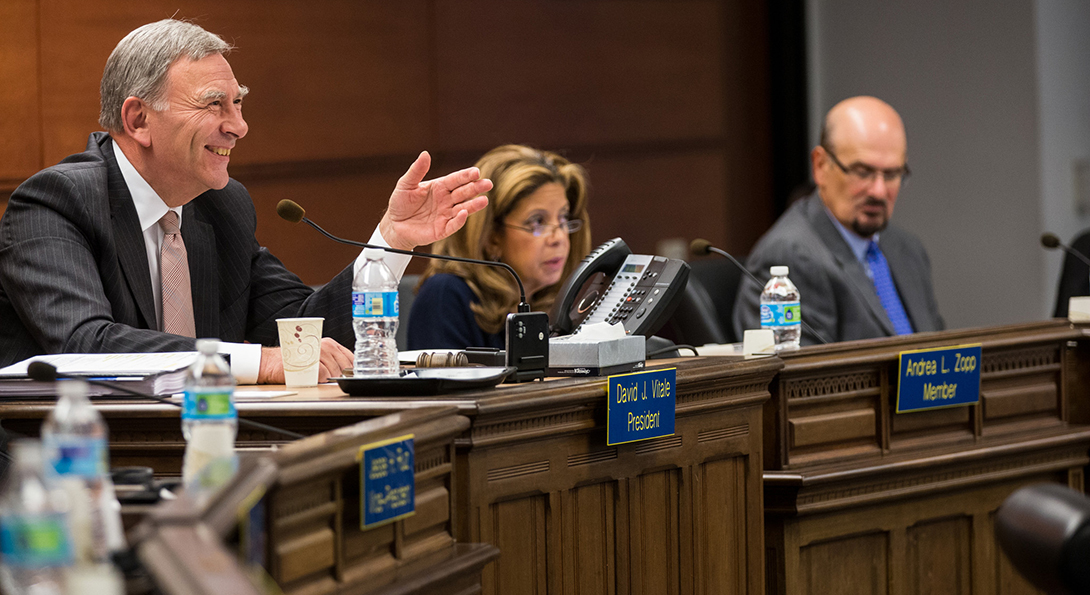 At a Chicago School Board meeting, board president David Vitale gestures to a speaker who is addressing the board, while two other board members are looking on at the interaction.