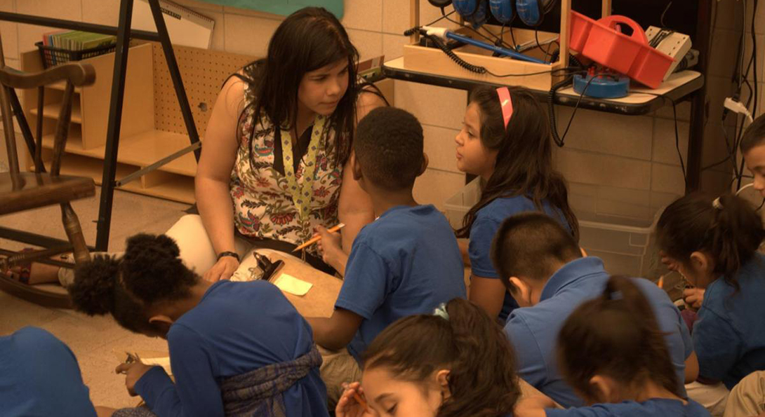 A teacher sits on the floor and talks with two Latino students who are working on an activity together, writing down responses on a clipboard.