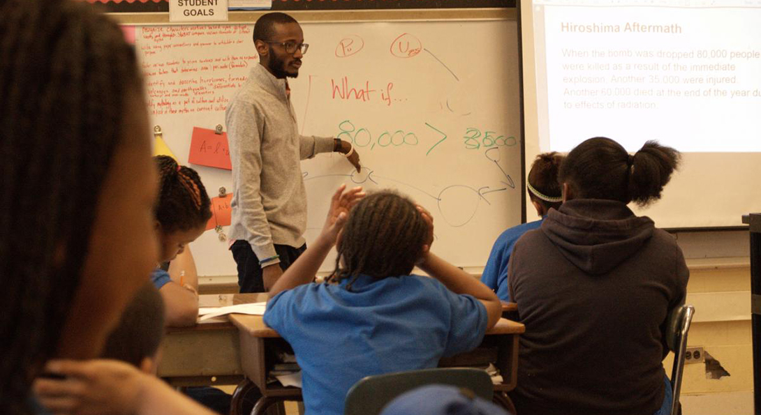 Evan Taylor teaches a math class, pointing to numbers and figures written on a whiteboard.  Students in his classroom are sitting at desks and listening to the lesson.