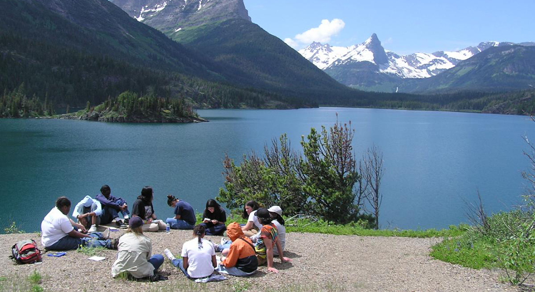 Girls sit in a circle on a sandy beach beside a lake surrounded by mountains as part of a Project Exploration trip.