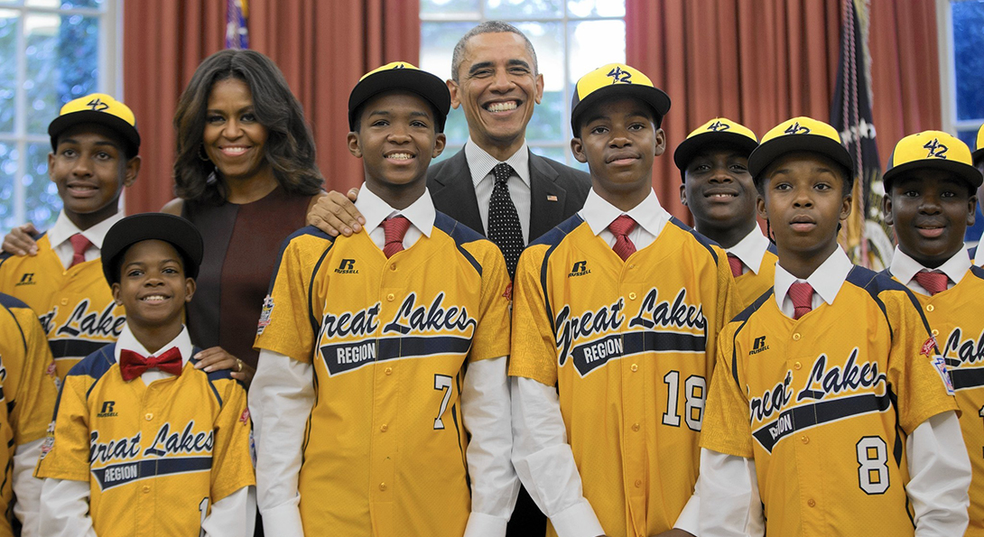 Kids on the Jackie Robinson little league team from Chicago pose with President Obama and First Lady Michelle Obama in the Oval Office.
