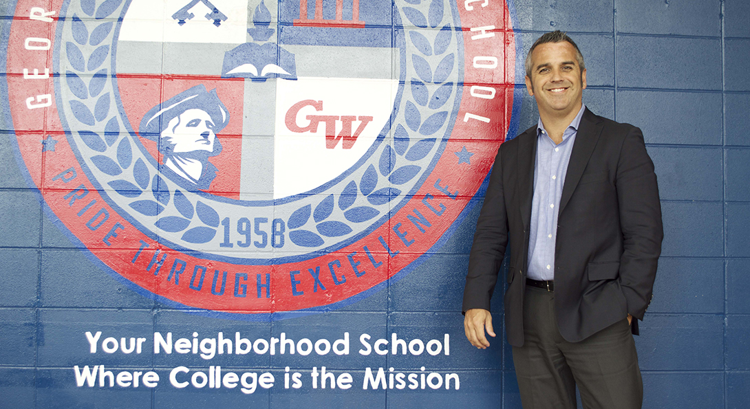 Principal Kevin Gallick stands next to the logo for George Washington High School, painted on a wall in his school, as he poses for a photo.