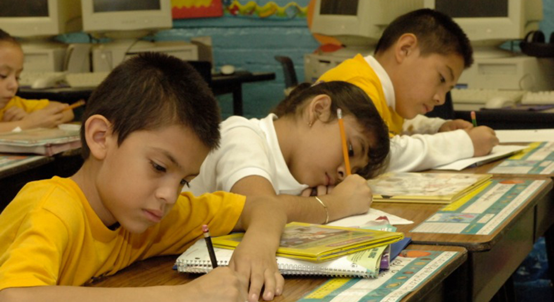 Three Latino students sit in a row at desks, each working on writing in workbooks.