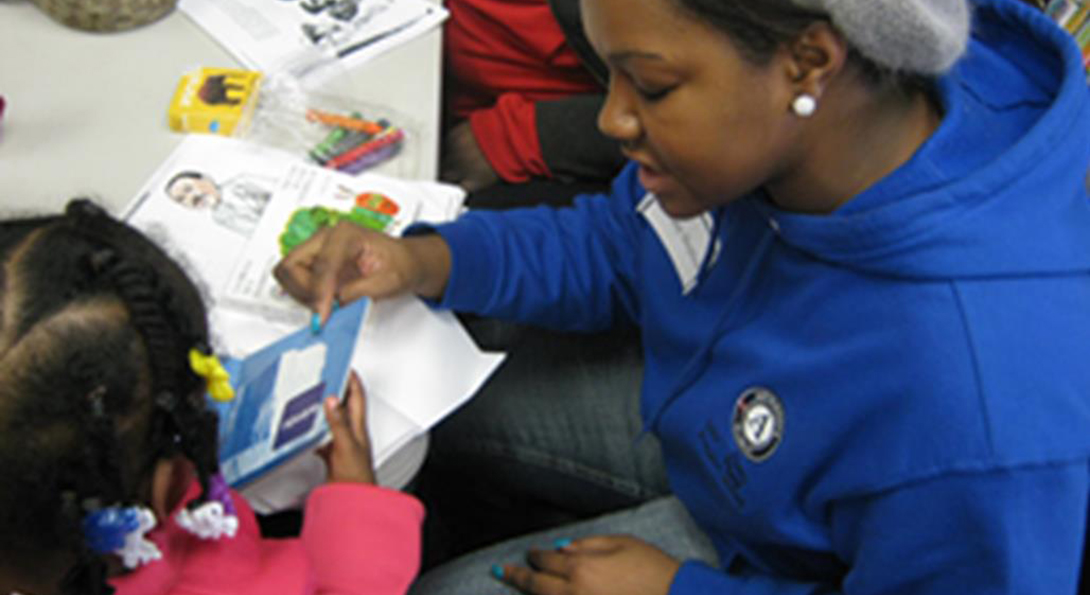 A volunteer reads a book to a young girl at the Center for Literacy's MLK Service Day.
