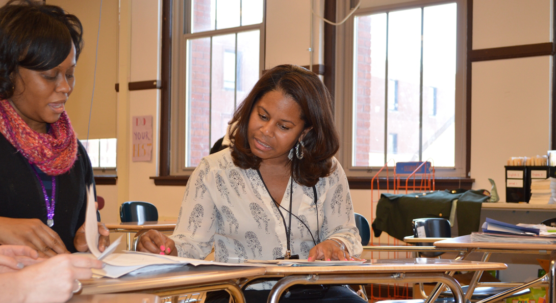 Principal Nia Abdullah sits at a desk in a classroom and is meeting with two teachers, discussing their lesson plans.