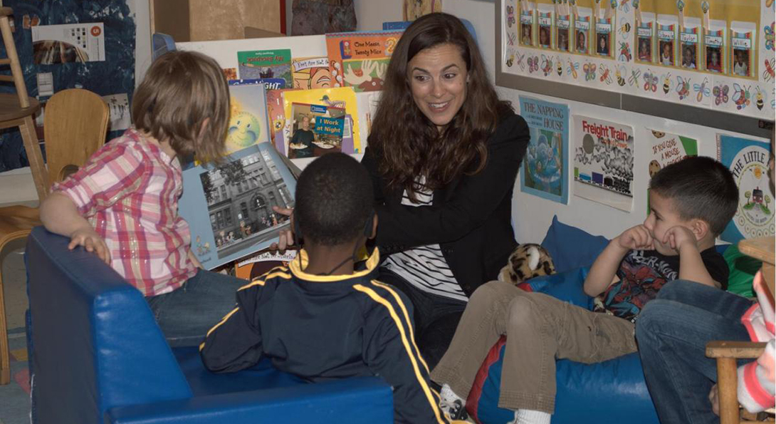 Samantha Richardson reads a book to a group of three children who are seated on the floor in a circle around her.