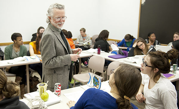 Profesor Mark Smylie stands amidst a horseshoe of three tables with students sitting at the tables.  He is talking with two female students while other students are talking amongst themselves.