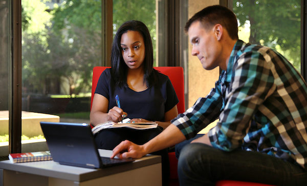 Two students are working together in the UIC Library.  A male student to the left is using the mouse on a laptop to navigate, while the female student to his right is looking at the computer screen and writing in a notebook.