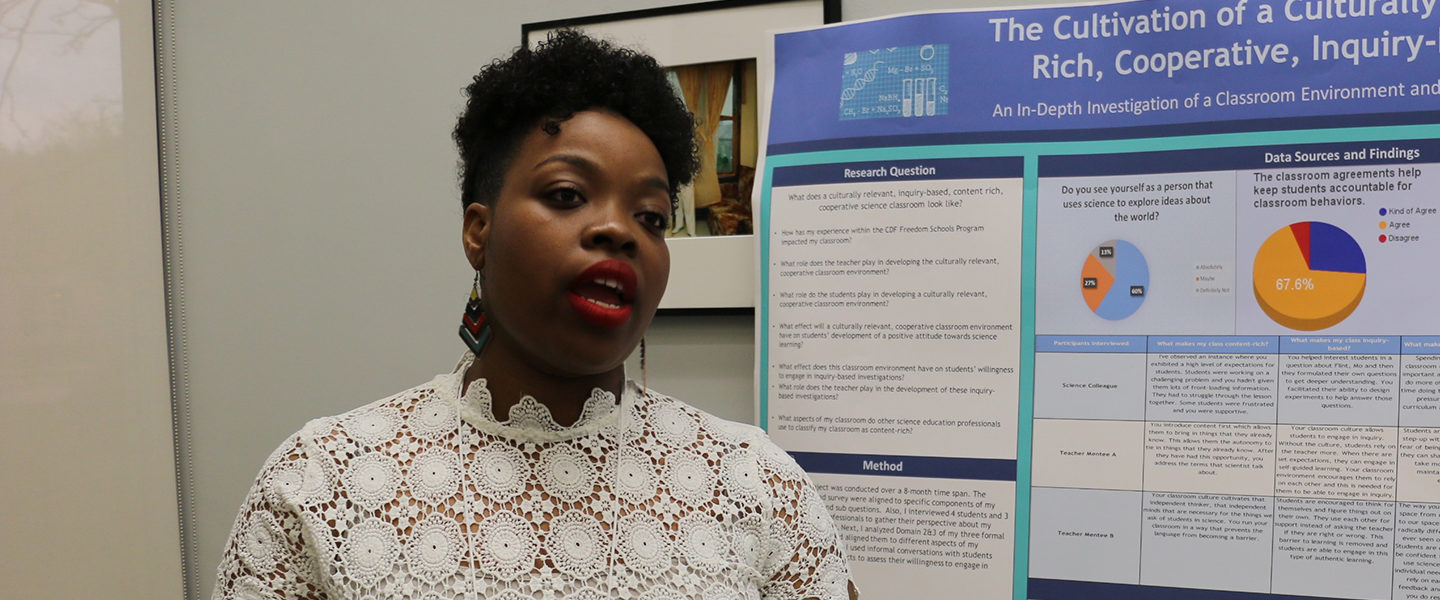 Student TaRhonda Woods discusses the results of her research project with a woman standing in front of her listening and a poster displaying her results behind her at a conference hosted by Project SEEEC, a grant project developing new science teachers to serve in Chicago Public Schools.