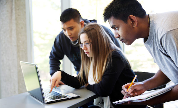 Three students are working on a group project, with a woman sitting working on a laptop and two male students standing beside her on either side, looking at the laptop and taking notes in a notebook.