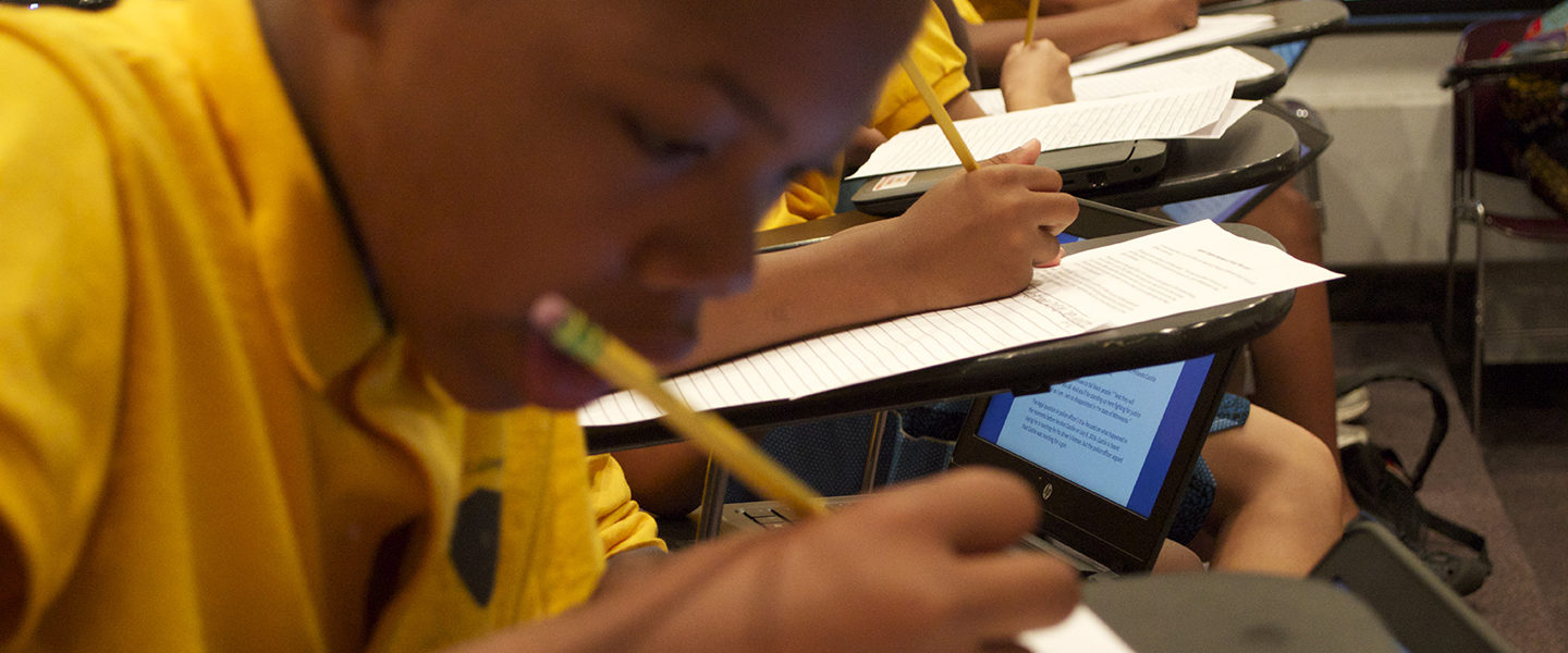 A Black boy sits at a desk, in a row with other students.  He, and the others, are all writing on pieces of paper with pencil, with laptops in their lap, which they are using to reference text.
